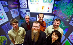 Purdue's DiaGrid team includes, from left, Andy Howard, Phil Cheeseman, John Campbell, David Braun, Preston Smith and Carol Song. The team is posing with images from the scientific research enabled by DiaGrid, projected in a multiwalled virtual environment at ITaP's visualization facility. (Purdue University photo/Andrew Hancock)