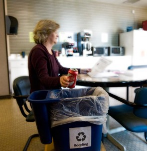Leslie Grey uses the new dual-stream recycling bins in Freehafer Hall. Purdue's new comprehensive recycling plan includes replacing desk-side trashcans with recycle bins. During the pilot phase, worker participation topped 99 percent and recycling volume nearly doubled. (Purdue University photo/Mark Simons)