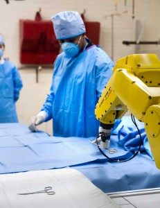 Mithun Jacob uses a prototype robotic scrub nurse with graduate student Yu-Ting Li